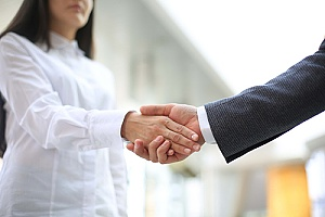 a business owner shaking hands with a map API developer after closing a deal