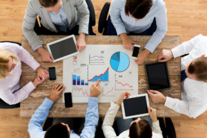 sales team look at many graphs and discuss how to improve growth of their sales