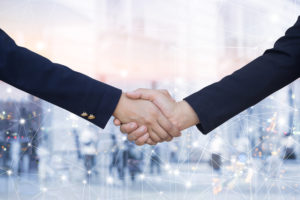 sales consultants shake hands before talking about a sales territory map